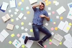 Jonge die mens op grijze achtergrond met slaperige documenten en nota's wordt geïsoleerd stock afbeeldingen
