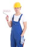 Jonge die mensenschilder in workwear met penseel op wit wordt geïsoleerd Stock Fotografie