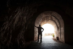 Jonge die mensentribunes in donkere tunnel worden ontspannen Stock Foto