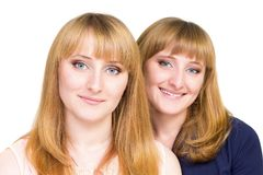 Jonge die tweelingenmeisjes op witte achtergrond worden geïsoleerd Stock Foto