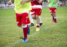 Jonge die voetbalsters in rode en witte overhemden in werking worden gesteld stock fotografie