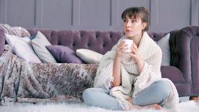 Jonge die vrouw in comfortabele pluizige de mokzitting van de plaidholding thuis wordt verpakt op wit tapijt stock videobeelden