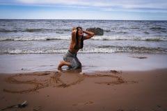 Jonge die vrouw dichtbij het overzees wordt verloren Stock Foto