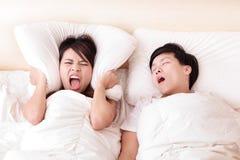 Jonge die vrouw door de gesnurken van haar echtgenoot wordt gestoord Stock Afbeelding