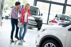 Jonge die vrouw door nieuwe auto wordt verrast Royalty-vrije Stock Foto