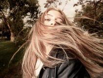 Jonge die vrouw met haar door wind wordt geveegd stock afbeeldingen