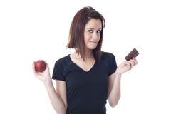 Jonge die vrouw tussen een chocoladereep en een verse appel wordt gescheurd Stock Foto