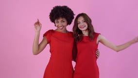 Jonge die vrouwenstudio bij het roze vrouwen` s dag stellen wordt geïsoleerd stock videobeelden