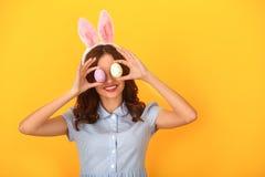 Jonge die vrouwenstudio op gele dragende konijntjesoren wordt geïsoleerd die ogen behandelen met eieren stock fotografie