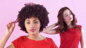 Jonge die vrouwenstudio op roze vrouwen` s dag wordt geïsoleerd wat betreft haar stock video