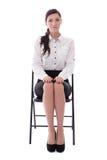Jonge die vrouwenzitting op bureaustoel op wit wordt geïsoleerd royalty-vrije stock afbeelding