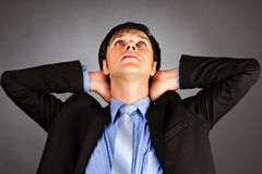 Jonge die zakenman met wapens achter hoofd worden gekruist Stock Fotografie