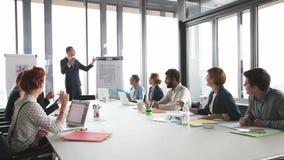 Jonge directeur die presentatie geven aan collega's in conferentieruimte stock footage
