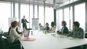 Jonge directeur die presentatie geven aan collega's in conferentieruimte stock videobeelden