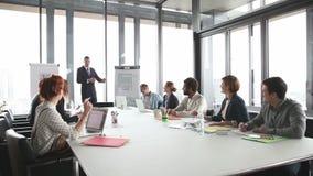 Jonge directeur die presentatie geven aan collega's in conferentieruimte stock video