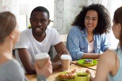 Jonge diverse vrienden die bij lijst in koffie zitten royalty-vrije stock afbeelding
