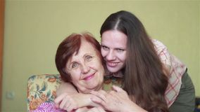 Jonge dochter benaderingen en zacht het koesteren van bejaarde moeder stock video