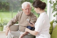 Jonge dokter die bloeddruk nemen stock foto