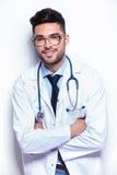 Jonge dokter met gekruiste handen stock afbeelding