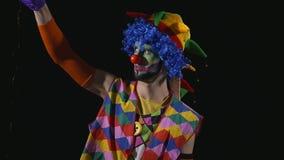 Jonge dolkomische clown die een lang haar uit trekken stock video