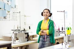 Jonge donker-haired Aziatische ontwerper in een groene cardigan die gelukkig glimlachen stock foto's