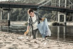 Jonge donker-haired vrijwilliger die zijn dag doorbrengen die het zand schoonmaken aan het strand royalty-vrije stock foto's