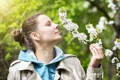 Jonge donkerbruin meisjes ruikende geur van bloemen op tak van tot bloei komende boom in de lente groene tuin in een heldere zonn Stock Foto's