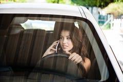 Jonge donkerbruine bestuurder die op celtelefoon spreken Royalty-vrije Stock Foto's