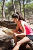 Jonge donkerbruine de kaartzitting van de meisjeslezing op logboek Royalty-vrije Stock Fotografie