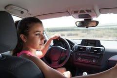Jonge donkerbruine die bestuurder van achterbank van auto wordt gezien Stock Fotografie