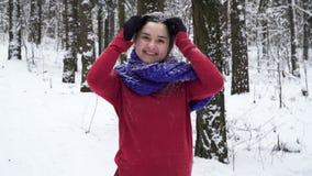 Jonge donkerbruine die vrouw met sneeuw in de winterbos wordt bestrooid stock video