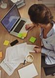 Jonge donkerbruine gebruikende laptop terwijl op het werk royalty-vrije stock afbeeldingen