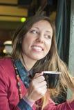 Jonge donkerbruine het drinken koffie bij een koffiewinkel Royalty-vrije Stock Afbeeldingen