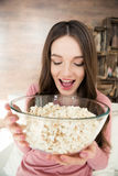 Jonge donkerbruine het glaskom van de vrouwenholding met popcorn Royalty-vrije Stock Foto