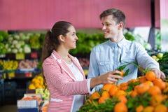 Jonge donkerbruine meisje en vriend het kopen citrusvruchten i Royalty-vrije Stock Foto's