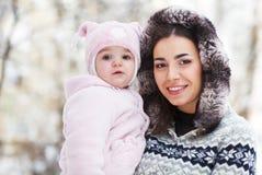 Jonge donkerbruine moeder met haar dochter in openlucht Royalty-vrije Stock Fotografie