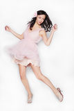 Jonge donkerbruine mooie vrouw die in roze die kleding danst over witte achtergrond wordt geïsoleerd Stock Afbeeldingen