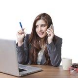 Jonge donkerbruine onderneemsterzitting die mobiele telefoon spreken bij haar Royalty-vrije Stock Foto