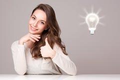 Jonge donkerbruine schoonheid met gloeilampensymbool Royalty-vrije Stock Afbeeldingen
