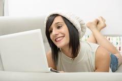 Jonge donkerbruine student die op de laag met laptop liggen Stock Fotografie