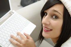 Jonge donkerbruine student die op de laag met laptop liggen Royalty-vrije Stock Afbeelding