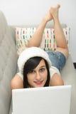 Jonge donkerbruine student die op de laag met laptop liggen Stock Afbeeldingen