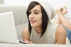 Jonge donkerbruine student die op de laag met laptop liggen Stock Foto's