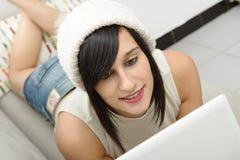 Jonge donkerbruine student die op de laag met laptop liggen Royalty-vrije Stock Foto