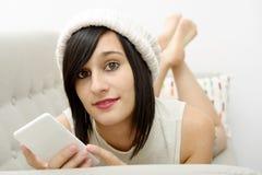 Jonge donkerbruine student die op de laag met telefoon liggen Royalty-vrije Stock Afbeeldingen