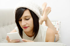 Jonge donkerbruine student die op de laag met telefoon liggen Royalty-vrije Stock Foto