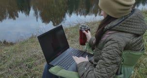 Jonge donkerbruine studente die aan laptop in aard werken Mooie de herfstdag en vrouw die van het genieten terwijl het gebruiken  stock footage