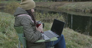 Jonge donkerbruine studente die aan laptop in aard werken Mooie de herfstdag en vrouw die van het genieten terwijl het gebruiken  stock videobeelden