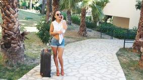 Jonge donkerbruine vrouw in borrels, zonnebril en hielen met koffer die op telefoon tussen palmen in de zomer spreken stock video
