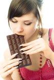 Jonge donkerbruine vrouw die chocolade eet Royalty-vrije Stock Afbeeldingen
